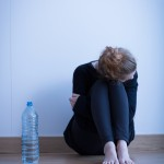 Upset young woman sitting on the floor
