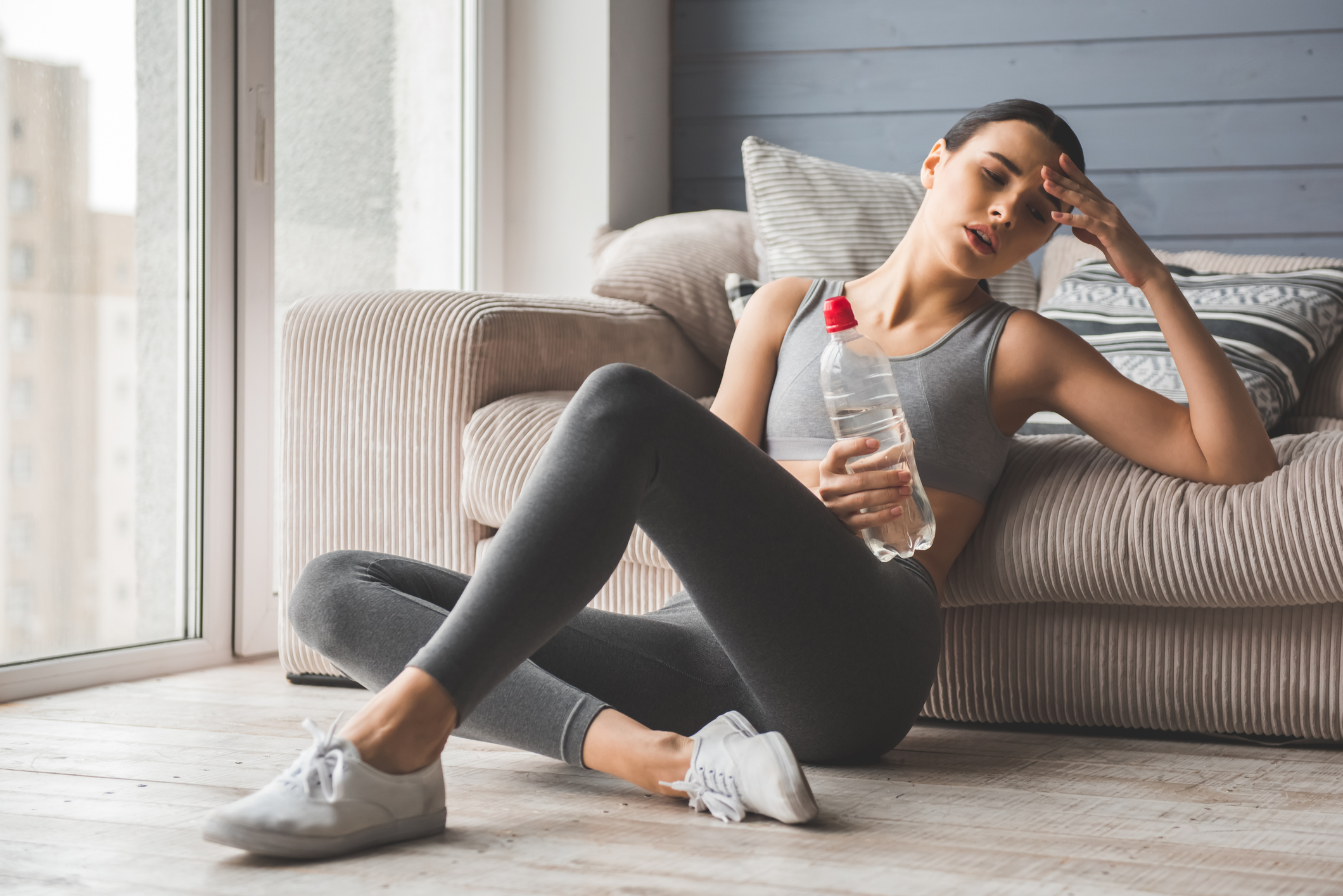 Young woman feeling faint, drinking water